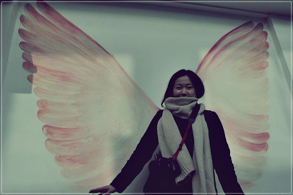 벽에 그려진 날개를 배경삼아 찍은 사진